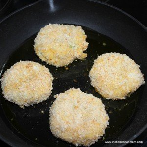 Four breadcrumb coated Irish cod fish cakes in a black pan