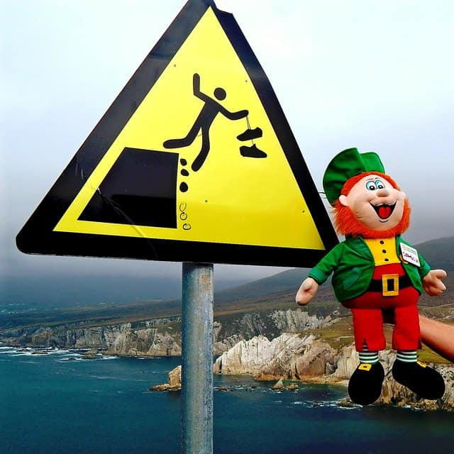 A red bearded leprechaun toy held beside a dangerous cliff sign