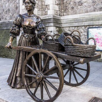 Sculpture of a woman with a wheelbarrow holding baskets