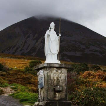 A white statue at the foot of a mountain