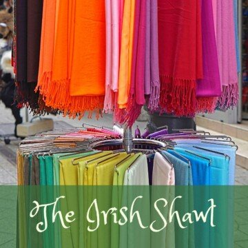 Shawls on a display rack with a text banner