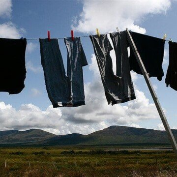 A clothes line with hanging clothes to dry with a view of the mountains in County Mayo Ireland