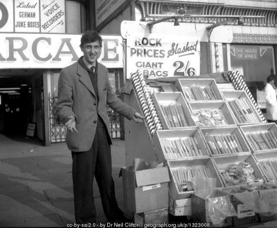 Vintage black and white image of a sweet vendor selling rock candy