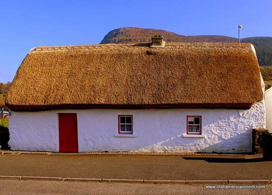 White washed walls of and Irish thatched cottage with red door