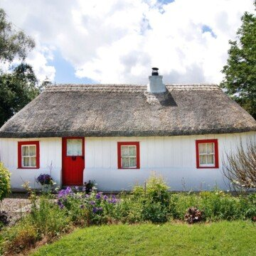 A white cottage with red door and windows with red frames and a thatched roof