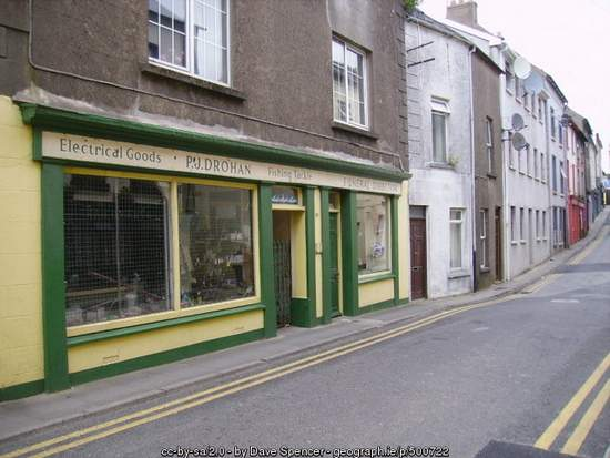 A street scene with focus on the side of a building and a shop front