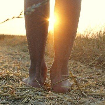 A woman walking barefoot in a field of straw