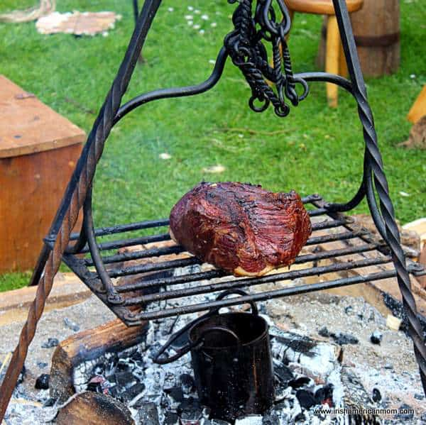 A beef joint on a metal tray over a fire
