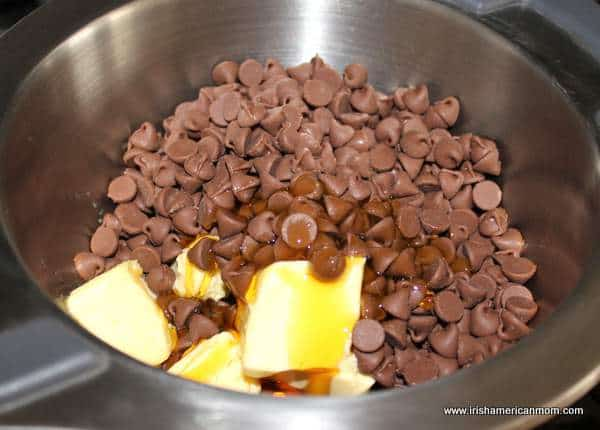 Melting chocolate chips, butter and golden syrup for biscuit cake
