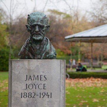Sculptured bust of a man on a pedestal in a park near a band stand