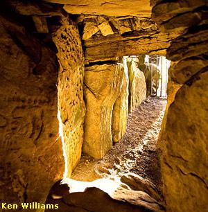A passage leading into a cairn or tomb with sun streaming through