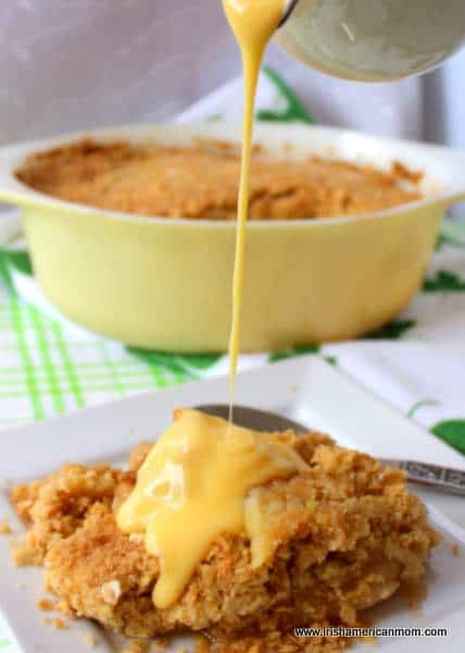 Pouring custard over apple crumble