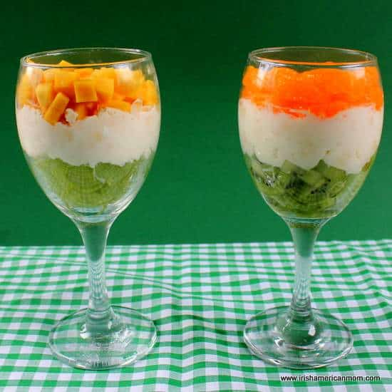 Layered fruit and cream desserts in wine glasses using orange and green colors of the Irish flag