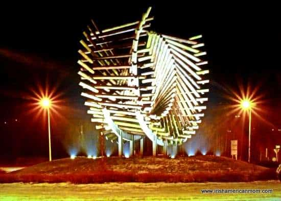 A wooden piece of art on a roundabout