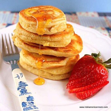 Stack of pancakes with dripping honey and a strawberry