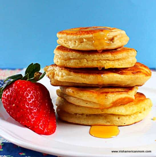 Irish buttermilk pancakes in a stack with honey dripping down the side