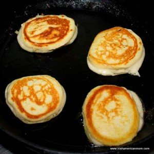 Flipped silver dollar pancakes in a cast iron pan