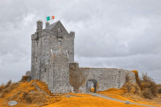 The Irish Flag flying over the old medieval Dunguaire Castle in Kinvarra, Galway