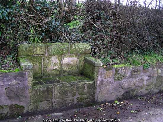 An old creamery stand that looks like a stone seat