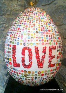 A large egg decorated with buttons and saying LOVE