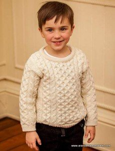 An Irish boy wearing a traditional natural color Irish Aran sweater