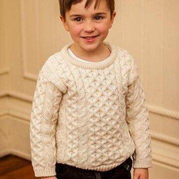 An Irish boy wearing a traditional natural color Irish Aran sweater