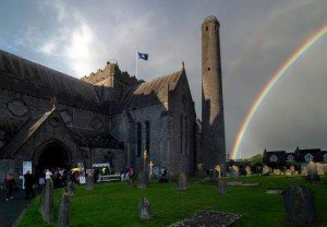 Rainbow in a cloudy sky beside the round tower at St. Canice's Cathedral