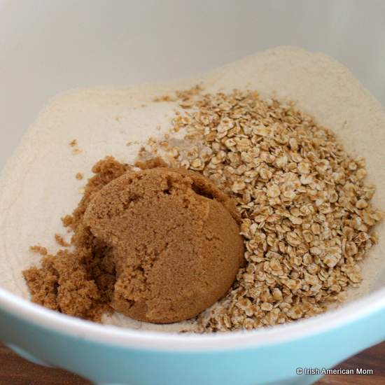 Adding brown sugar and oatmeal to flour for blueberry banana muffins