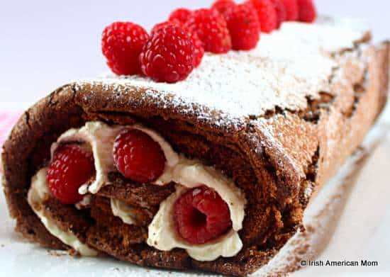 Chocolate roulade or cake roll decorated with fresh whipped cream and raspberries