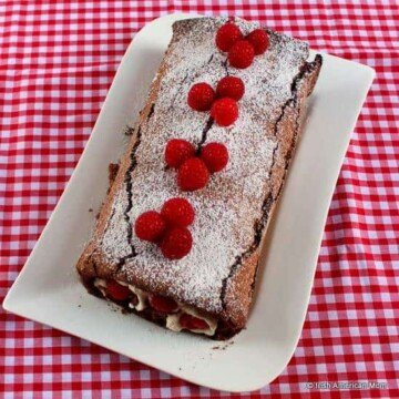Chocolate raspberry and cream roulade on a white plate with red gingham table cloth