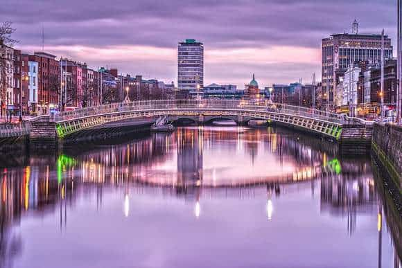 Ha'penny Bridge or Halfpenny Bridge reflecting in the River Liffey in Dublin