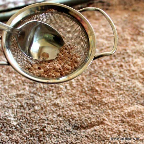 Sifting confectioner's sugar and cocoa powder on top of a chocolate roulade