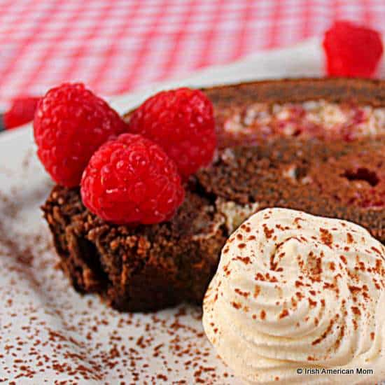 Slice of raspberry chocolate roulade or swiss roll with fresh whipped cream