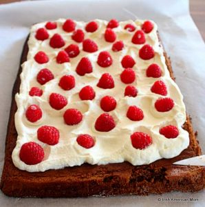 Spreading heavy whipping cream and raspberries inside a chocolate roulade before rolling