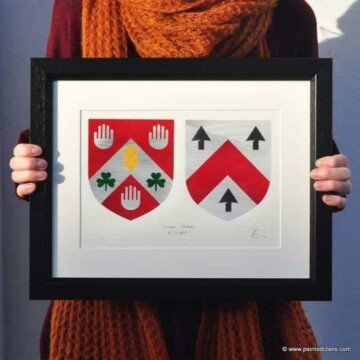 Woman holding a framed art piece featuring coats of arms
