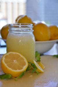 A jar of lemonade with a bowl of lemons