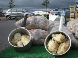 Floury Irish potatoes in saucepans on display at a market