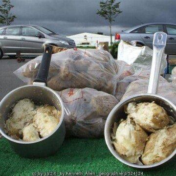 Floury Irish potatoes in saucepans on display at a market