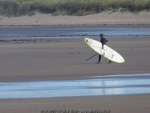 carrying a surf board on an Irish beach
