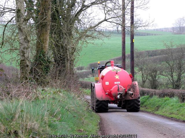 A dung spreader being pulled by a tractor