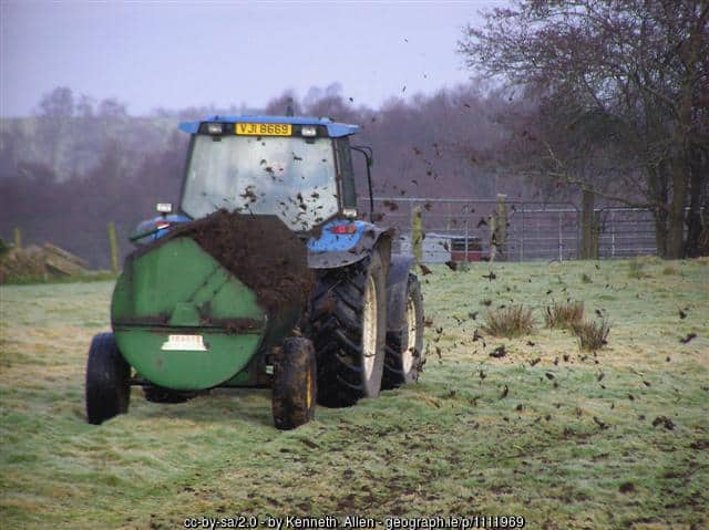 Spreading manure with a tractor in a field