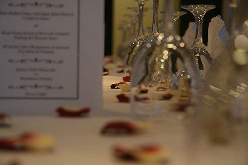 The wedding table strewn with rose petals