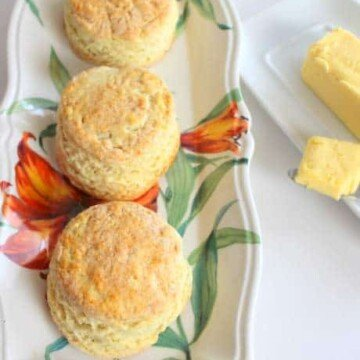 Three freshly baked Irish scones with butter on the side