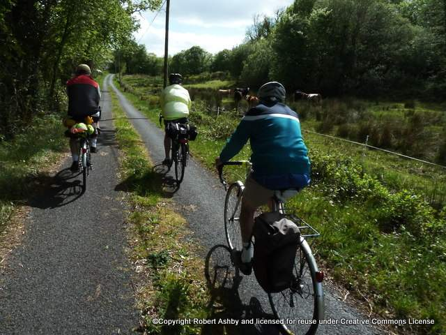 Cyclists on the side of a narrow road