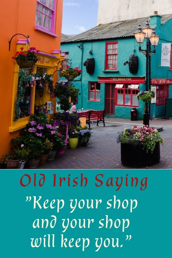 Brightly colored store fronts in an Irish village with flowers outside a flower shop