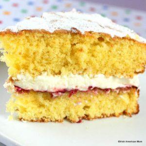 Slice of Victoria sandwich cake on white plate