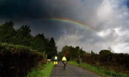 Rainbow in a cloudy sky over cyclists on an Irish road