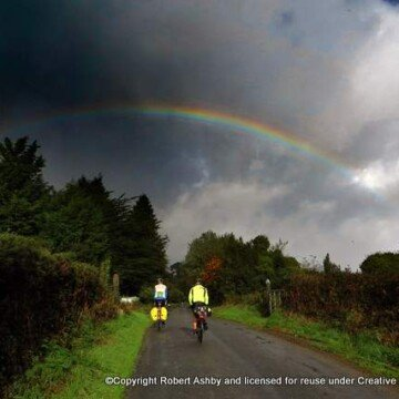 A rainbow over a road with cyclists