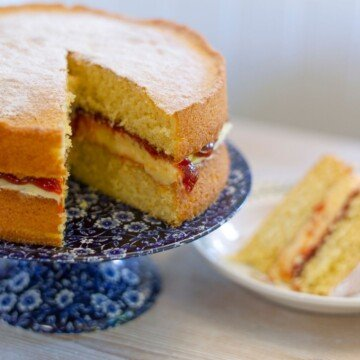 Cream sponge cake on a stand with a slice removed