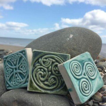 Three Celtic design tiles sitting on a rock by the ocean